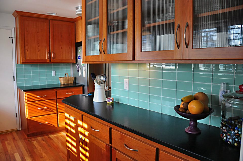 this glassy turquoise backsplash adds a beachy surf inspired vibe to