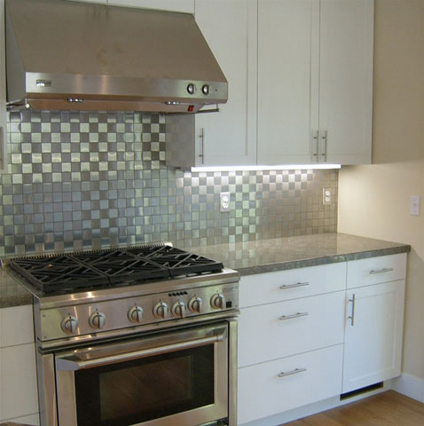 modern than stainless steel appliances, this faux stone backsplash ...